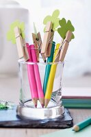 Coloured pencils topped with clothes pegs holding paper shamrock leaves