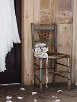 Bouquet of roses on an old chair in front of a wooden wall, wedding dress hanging from a wooden door