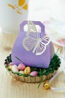Easter gift in gift box with paper butterfly in Easter nest in tart tin