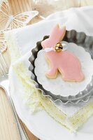 Rabbit-shaped biscuit with pink icing and small bell in tartlet tin