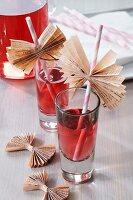 Straws decorated with wings of folded newspaper