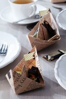 Newspaper boats filled with chocolates as table decorations