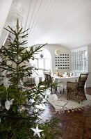 Christmas tree decorated with white stars and glass baubles; dining room with wood-clad, white-painted barrel vaulted ceiling and mosaic parquet floor