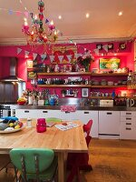 Kitchen counter along hot pink wall with long wooden shelves; simple wooden table with colourful retro chairs in foreground