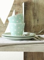 Polka dot cups and plates and cutlery on wooden surface