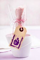 Plastic cutlery and pink linen napkin in beaker; wooden tag with rubber-stamped cake