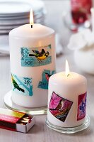 Stamps with bird motifs stuck on pillar candles