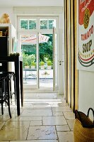 Bentwood stools at black counter in kitchen with limestone flags; view of terrace through French windows