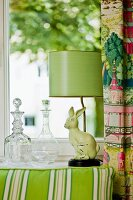 Glass carafes and green retro lamp with rabbit figurine as base on windowsill