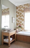 Simple washstand with white basin below mirror and bathtub against wall with retro wallpaper