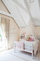 Vintage child's bed with canopy hanging from sloping attic ceiling next to window with gathered curtain