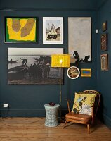 Small, vintage armchair next to standard lamp with yellow lampshade below gallery of pictures on wall painted blue-grey