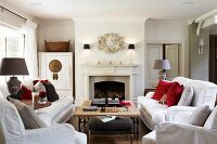 White sofas and coffee table in front of open fireplace in traditional, elegant country house