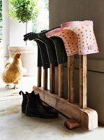 Wellington boots on vintage wooden rack; hen on veranda in background