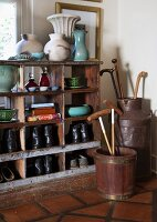 Various walking sticks of different styles in vessels next to shoes and ornaments on half-height shelving