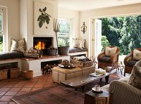 Various seats around rustic coffee table in country-style living room with open fireplace; view into garden through open folding doors in background