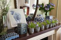Purple flowering plants in china beakers in front of painting of sheep and ceramic vessels on mantelpiece