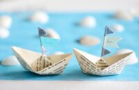 Paper boats with names on flags as place cards