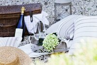 Romantic picnic with cushions, sparkling wine and picnic basket on gravel floor