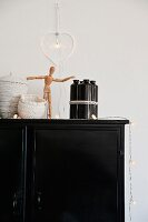 Various containers, artists' wooden mannequin and light art objets d'art on black cabinet