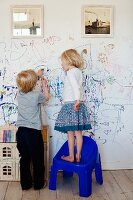 Two children scribbling on a white wall below framed photographs