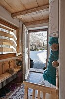 Open front door in foyer of wooden chalet with view of snowy landscape