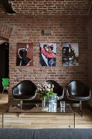 Plexiglass coffee table & bench with brown, leather-covered shell seats below portraits of women on brick wall