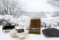 Various animal skins on chairs, table, cushion and as rug in snow