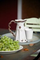 Vintage ceramic jug and beaker on metal tray next to plate of grapes