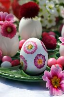 Easter table decoration with fresh flowers and egg decorated using napkin decoupage