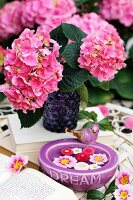 Pink hydrangeas in purple glass vase