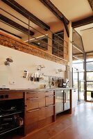 Modern kitchen counter below gallery with metal balustrade in renovated farmhouse