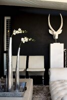 White flowers in metal vases on tray and white chairs next to animal-head sculpture against black wall
