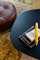 View down onto black metal table and brown leather pouffe on patterned rug