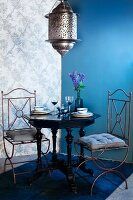 Moroccan-style pendant lamp above antique table and two wire chairs in corner of room with one blue wall and patterned wallpaper