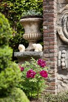 Romantic arrangement of planted urn, cat figurines and flowering peony in garden