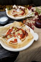 Small pizzas and baking parchment on rustic plates and arrangement of vine foliage on garden table
