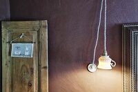 Pendant lamp with lampshade upcycled from old teacup against mauve wall; sign hanging on rustic wooden panel