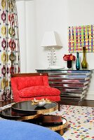 Modern interior with red armchair and chrome console table; modern artwork on wall