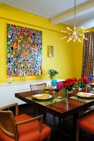 Solid wood dining table in yellow room with colourful, modern paintings and star-shaped pendant lamp