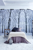 French bed with knitted blanket and scatter cushions on floor covered in artificial snow in front of poster of winter landscape