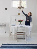 Woman in white dining room with set dining table & chandelier