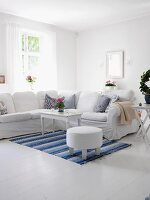 White living room with large corner sofa & blue and white rug