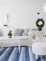 Swedish-style living room with white sofa & blue and white rug