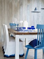 Blue and white dining room with wooden table & various chairs