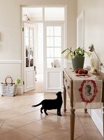 Flower arrangement and runner on sideboard in pale country-house kitchen with black cat on tiled floor