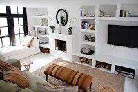 View down into lounge area with ottoman and rug in front of TV on masonry shelving in rustic ambiance