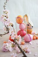 Easter arrangement of dyed eggs, chocolate rabbit & sprig of cherry blossom