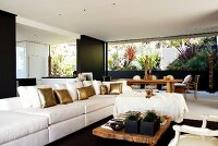 Long sofa with white and golden scatter cushions, low, rustic coffee table and dining area in front of patio with planted beds