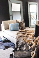 Daybed with animal-skin blanket and scatter cushions and full-length, framed mirrors leaning against wall